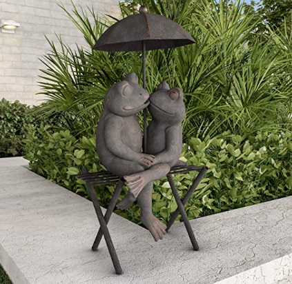 A sculpture of two frogs kissing each other underneath an umbrella..