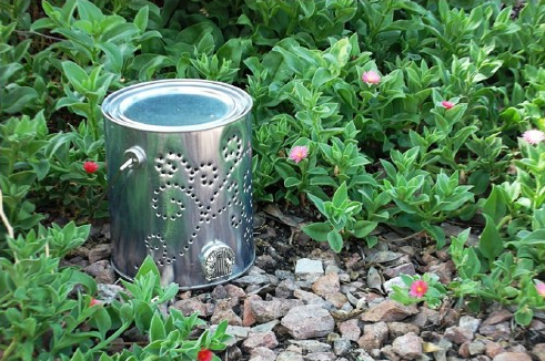 A silver aluminum paint can with holes punched into it to make a cute design standing upright on small rocks