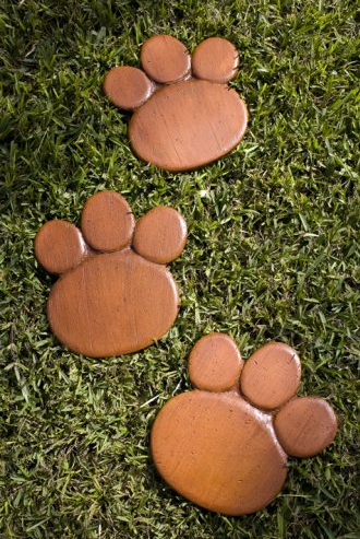 Three brown stepping stones in the shape of dog paws.