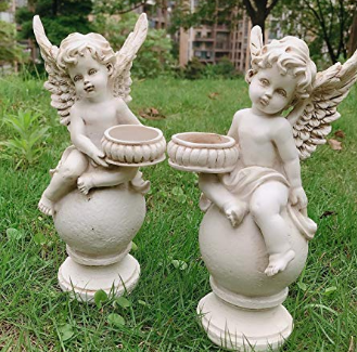 A statue of two baby angels standing upright on grass