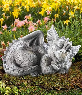 A small silver statue of a dragon laying on garden soil