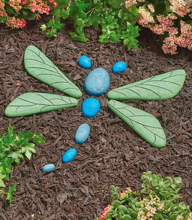 A bunch of rocks shaped into a dragonfly that is blue and green in color laying on brown mulch
