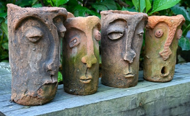 Four long faced statues beside each other.