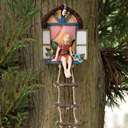 A decoration of a fairy sitting out of a window above a ladder placed on a tree trunk.