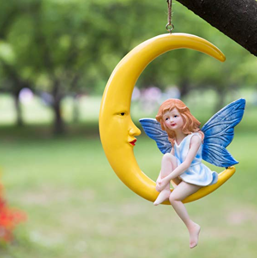 A decoration of a blue fairy sitting on a half yellow moon hanging from a tree.