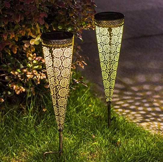 Two cylindrical solar lights with neat patterns stuck in garden soil.