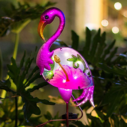 A pink flamingo light decoration placed in a garden.