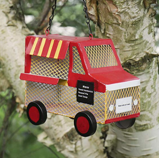 A red food truck bird feeder hanging from a tree branch.