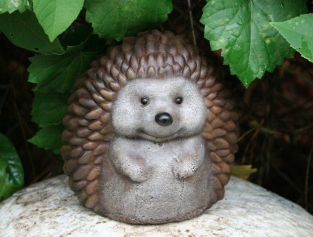 A tiny brown hedgehog ornament sitting on a rock in the garden