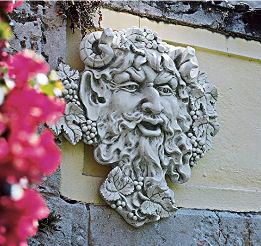A bearded face concrete sculpture planted on an outdoor concrete wall.