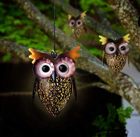Three owl decorations hanging from a tree.