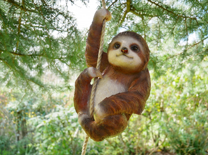 A large sloth decoration hanging from a rope tied around a tree branch.