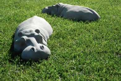 Two large hippo sculptures laying on grass.