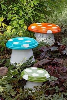 Orange, blue and green homemade mushroom chairs placed in a garden.