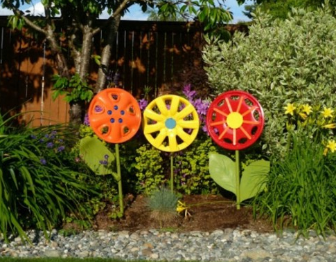 3 colored hubcap homemade flower designs aligned standing up right in a garden