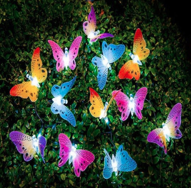 A bunch of lit up butterfly ornaments in a green bush
