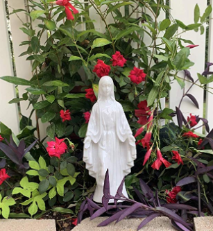 A white Mother Mary statue standing upright