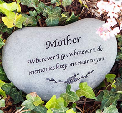 """A grey smooth stone with the word """"Mother"""" engraved into it."""