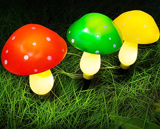 Three lit up mushroom decorations red, green and yellow in color placed on grass.
