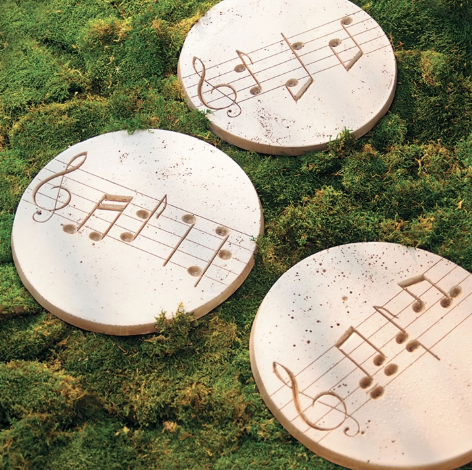 Three beige stepping stones resting on grass with music notes engraved into them.