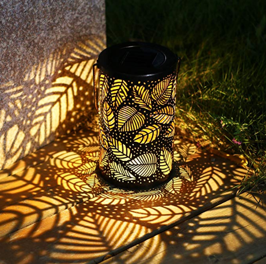 A cylindrical solar light with leaf decorations on it in the nighttime darkness.