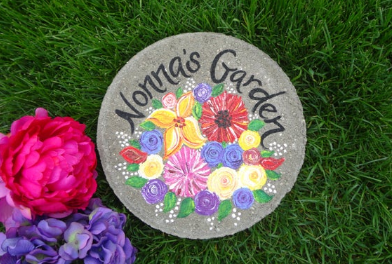 """A circular stone with painted flowers on it and the words """"Nonna's Garden"""" engraved into it."""