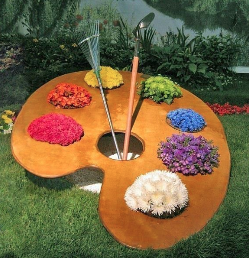 A large garden decoration of a paint palette with flowers as the paint colors