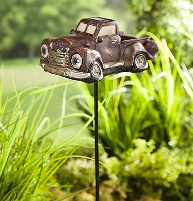 A 1950s pickup truck decoration inserted into garden soil