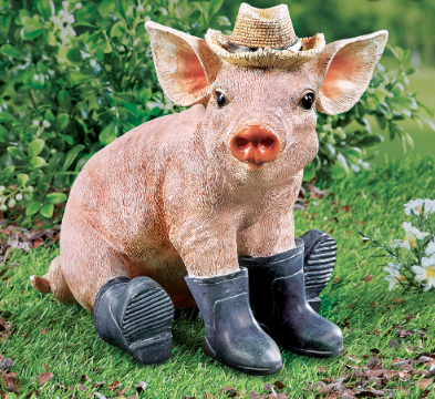 A pig garden ornament wearing black boots and sitting down on grass