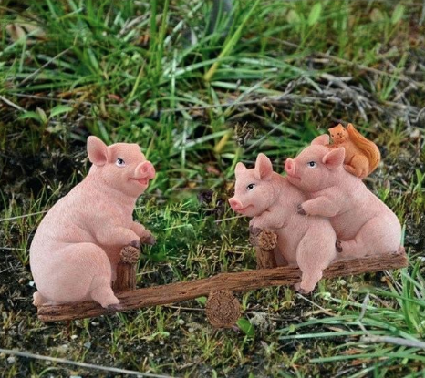 A garden ornament of three pigs on a wooden seesaw with a squirrel on one of their heads