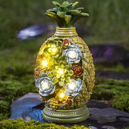 A colorful nightlight pineapple decoration standing upright on a flat rock