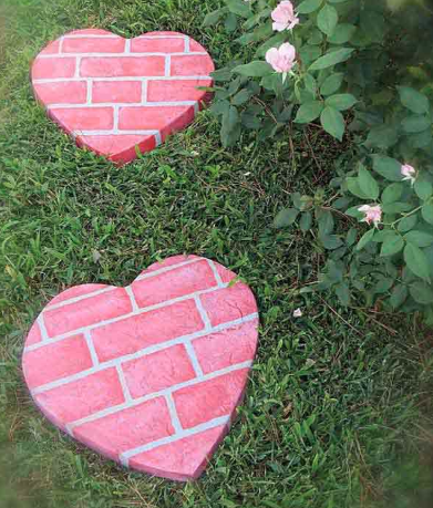 Two heart-shaped stepping stones made out of brick and colored pink laying on grass.