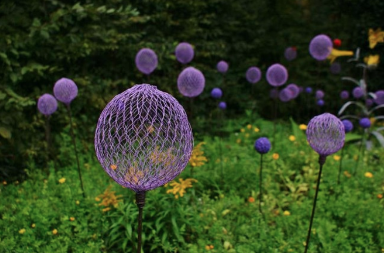 A bunch of purple balls made out of chicken wire sticking in a garden.