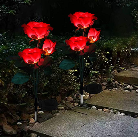 Six red rose lights that are stuck in garden soil.