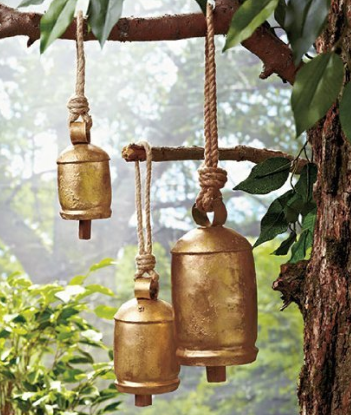 Three rustic wind chimes hanging from a tree