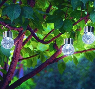 Three silver lit balls hanging from a tree with green leaves.