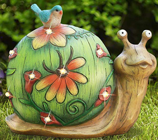 A solar light turtle decoration green and red in color standing upright on grass.