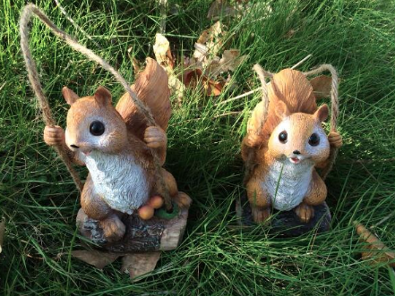 Two squirrel ornaments sitting on grass