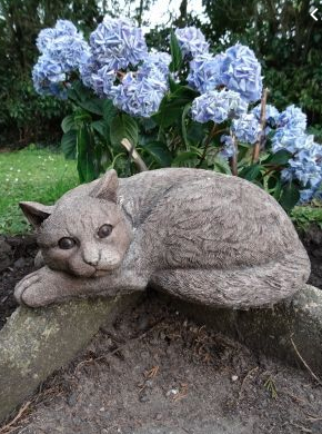 A cat made of stone laying on a rock