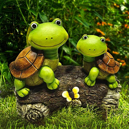A sculpture of two green turtles sitting on top of a brown log