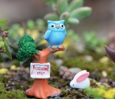 A garden ornament of a little blue bird sitting on a brown plastic tree branch