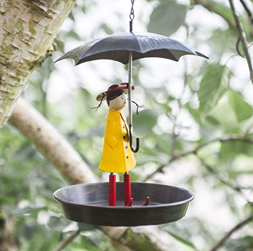 A bird feeder designed with a woman wearing a yellow jacket and holding a silver umbrella.