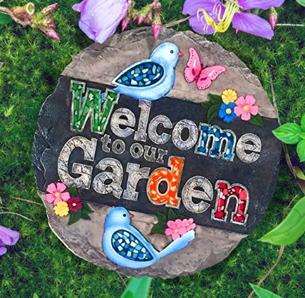 A stepping stone that reads welcome to our garden in colorful letters.