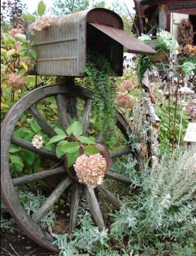 A decoration of a wooden wheel with a mailbox resting on top of it.