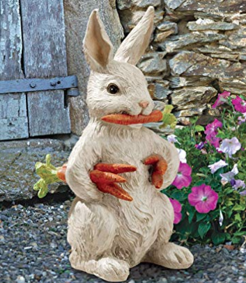 A white stone bunny ornament with orange carrots in its mouth and hands sitting on concrete