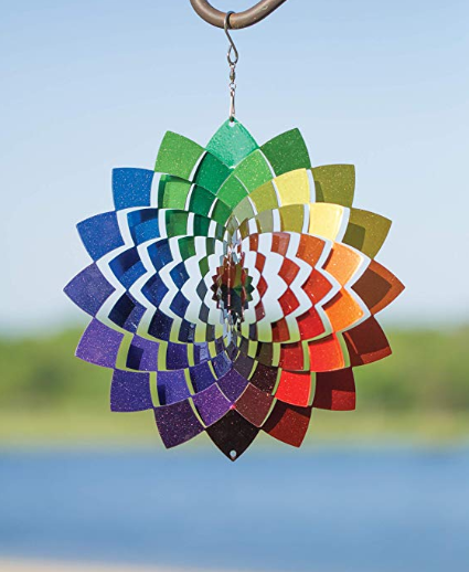 A colorful wind spinner decoration hanging outside in the blue sky.