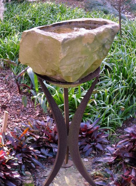 Sculpted stone birdbath placed at the top of an iron stand.