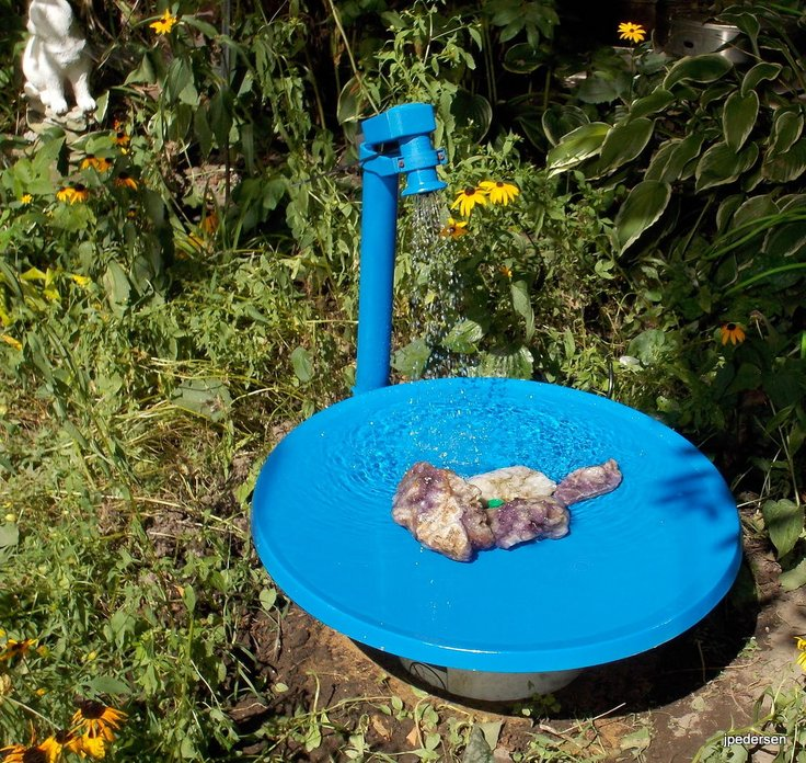 Satellite dish birdbath painted with blue.
