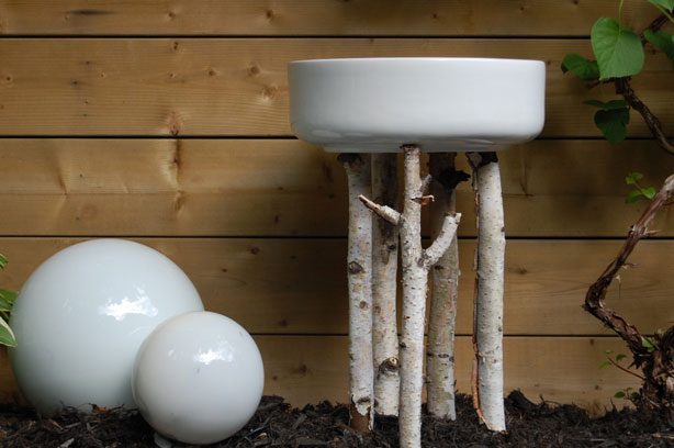 Birch twigs with ceramic bowl birdbath.