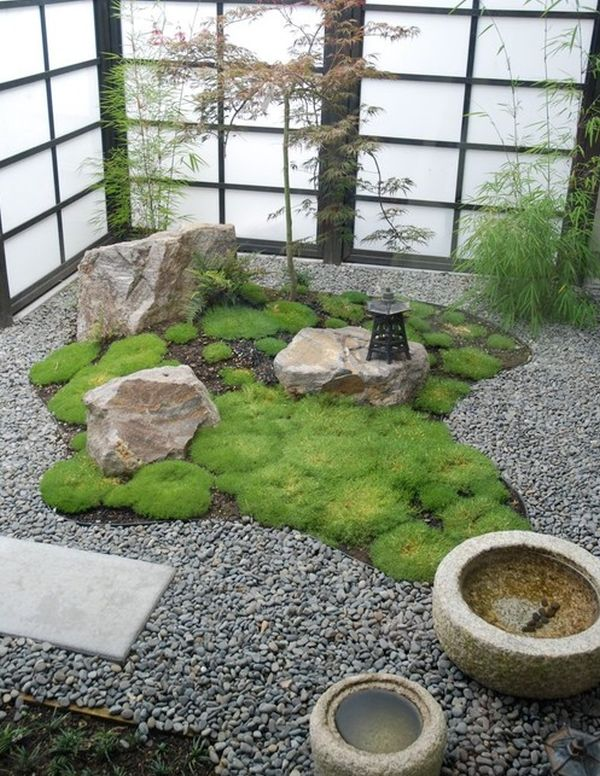 A compact garden in a corner composed of rocks, moss and gravels.